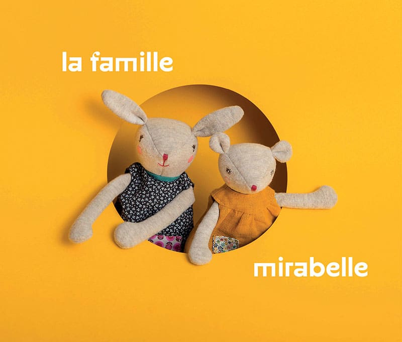 two rabbits looking out from a round hole in a yellow background 'la famille mirabelle'