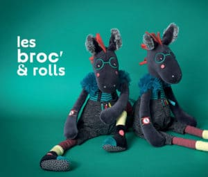 two black plush horse dolls sitting on a green background 'les broc and rolls'